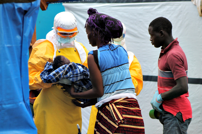 © Martin Zinggl/MSF: An MSF doctor takes a child whose mother died from Ebola in the CMC, 2014.