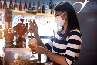 Bartender wearing a face mask pours a glass of beer via iStock / LeoPatrizi
