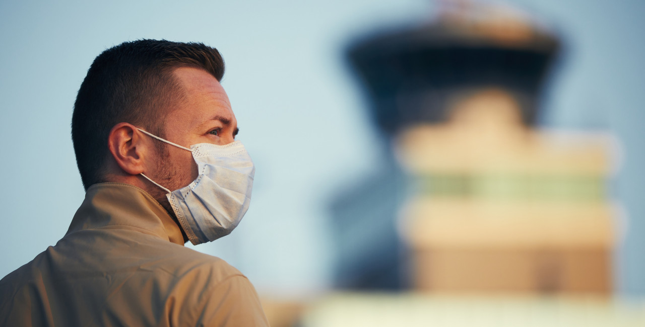 A man wearing a face mask outside Prague airport, via iStock.com / Chalabala