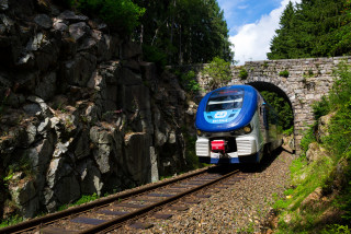 Ceske drahy CD railway train passes under a stone bridge in the Ore Mountains in Nejdek, Czech Republic. (photo: iStock / josefkubes)