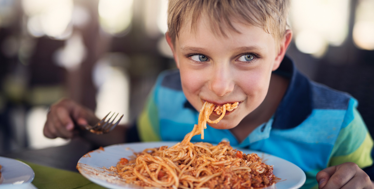 Happy little boy aged 7 is eating spaghetti lunch. iStock/ Imgorthand