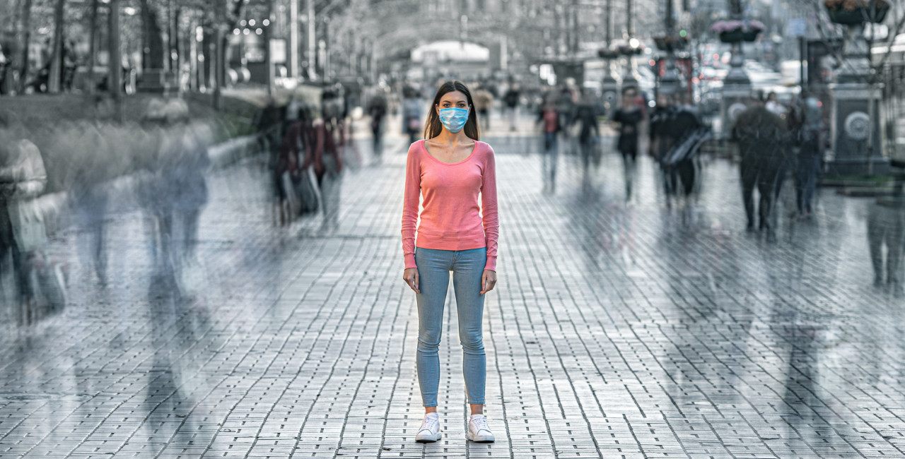 Woman in mask on street, blurred passersby. (photo: iStock /  Viacheslav Peretiatko)