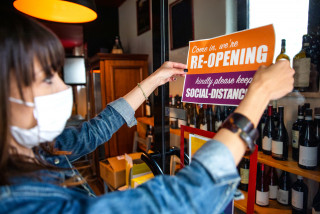 A woman places a sign in a shop window, via iStock / LeoPatrizi