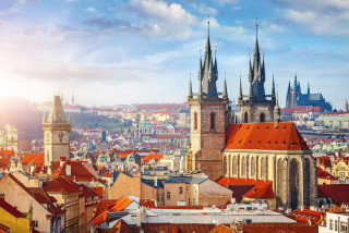Church spires and rooftops in central Prague via iStock / Yasonya