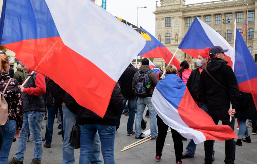 People gather atop Wenceslas Square draped in Czech national flags during the rally. (photo: James Fassinger - Expats.cz)