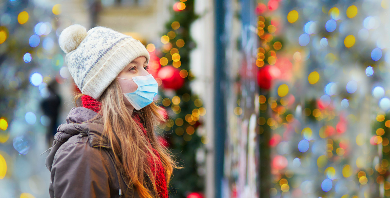 Girl wearing face mask during Christmas holiday season via iStock / encrier