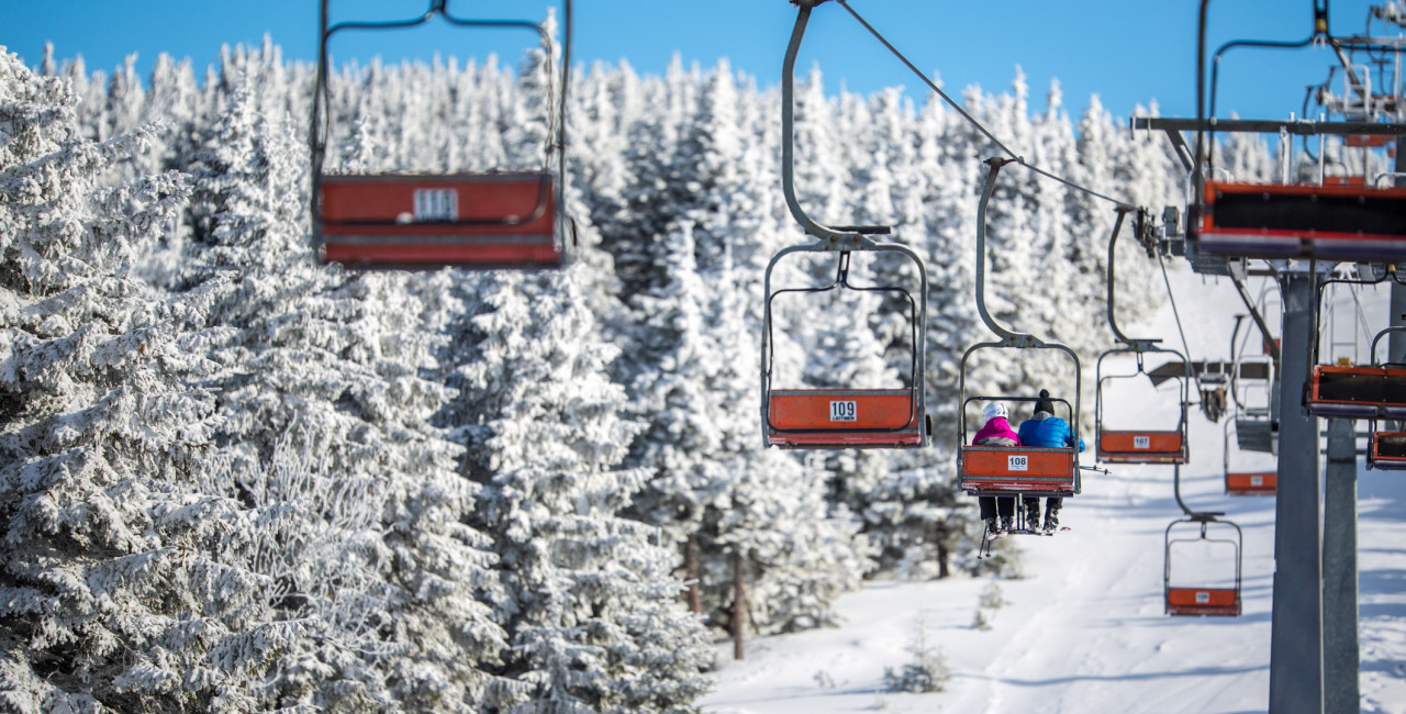 Skiers riding a chairlift via iStock / ViktorCap