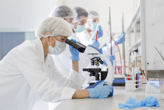 Scientists examine a virus in the laboratory, via iStock / Nastasic